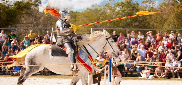 A knight in tin armor on the back of a galloping horse at a Medieval Fair.