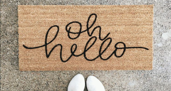 A hello mat placed outside a front door of a home or apartment.