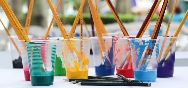 Plastic cups filled with paint and water with paintbrushes at an art class.