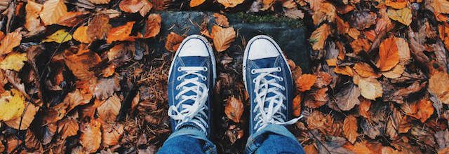 Shot of mans feet in fall colored leaves