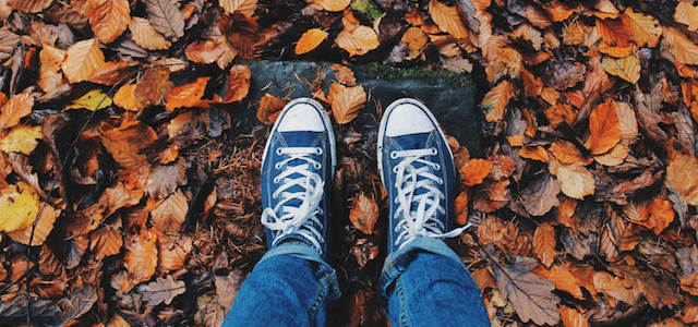 Two feet walking on autumn leaves outside.