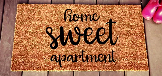 "A brown door mat with ""Home Sweet Apartment"" text."
