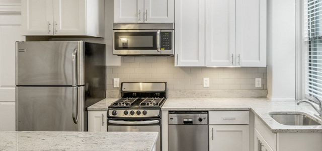 An interior view of a renovated kitchen with white cabinets and high end appliances at The Parkside in Boston.