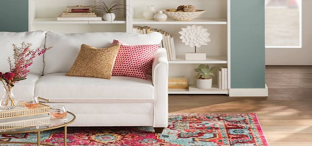 A brightly colored living room with a white couch, throw pillows, and a multicolored area rug.