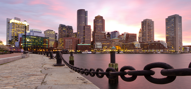The skyline of downtown Boston along the harbor at sunset.