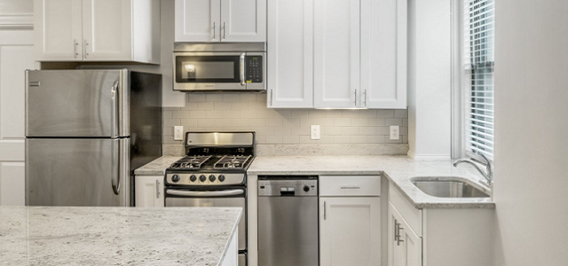 An interior view of The Fenway & Back Bay Portfolio apartments updated white kitchen and stainless appliances.
