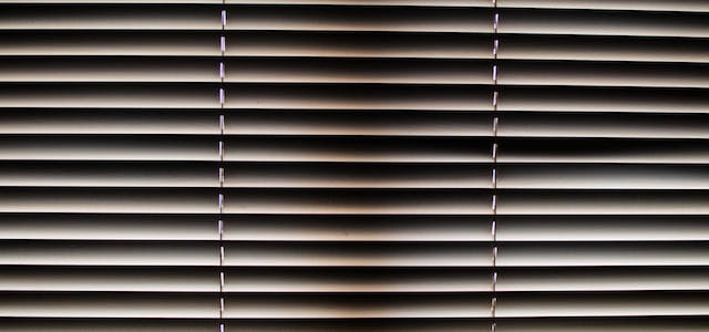 A window covered with blinds and sunlight shining through.