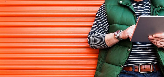 A man standing in front of an orange storage unit looking at an iPad.