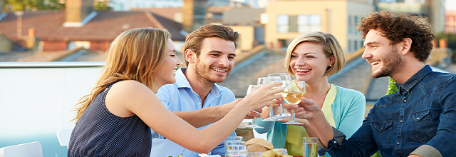 Group of young people eating and drinking wine outside