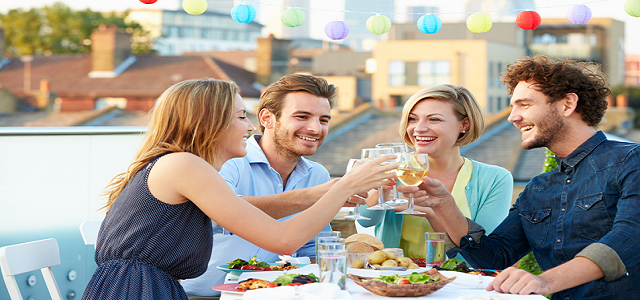 A group of friends toasting outdoors at dinner.