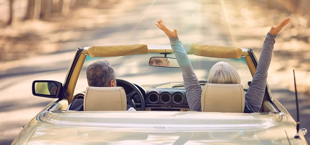 An elder couple driving a convertible down a road.