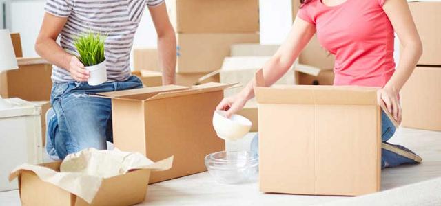 Two roommates unpacking belongings from brown cardboard boxes.