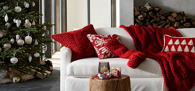 a white couch decorated with a red throw blanket and decorated christmas tree photo credit crate barrel - Crate And Barrel Christmas Decorations