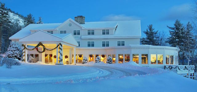 A front entrance view of White Mountain Hotel decorated with wreaths and warm lights.