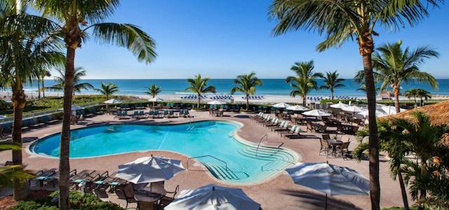 The outdoor pool at Siesta Key Palms Hotel in Sarasota, FL next to a white sand beach.