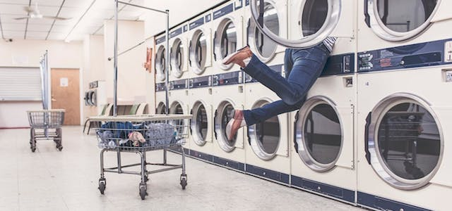 A man dangling his feet out of a washing machine looking for clothing.