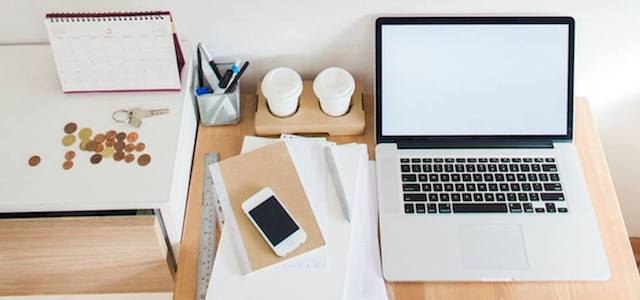 A wooden desk with silver laptop, smart phone, and office supplies.