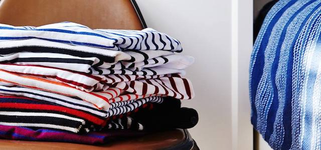 A pile of neatly folded stripped shirts and clothing.