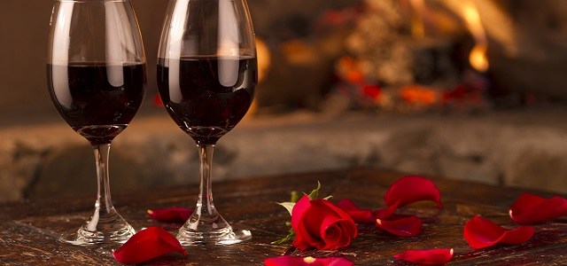 Two red wine glasses in front of a glowing fire with red rose petals.