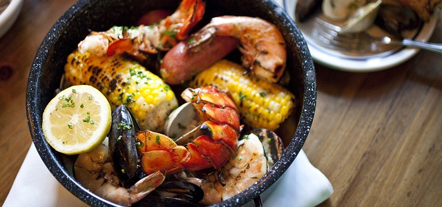 A bowl of fresh seafood and corn.