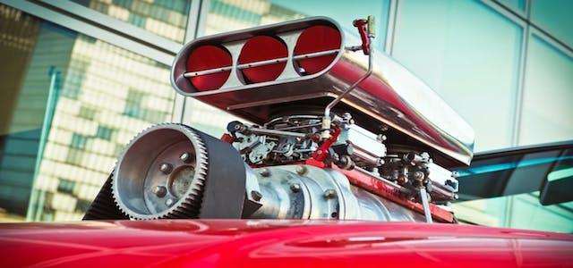 A bright red hot rod car with a silver engine on the hood.