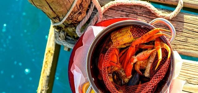 A bucket of fresh crab legs on a pier.