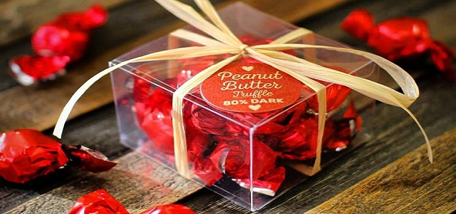 A clear box with peanut butter truffles wrapped in red foil from Taza Chocolate.