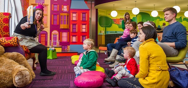 Story time with children and parents in a colorful room at the Boston Public Library.