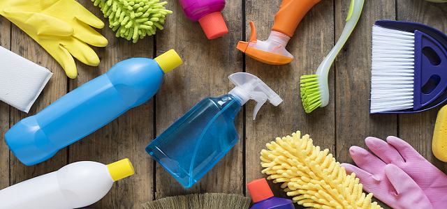 Colorful cleaning bottles and supplies on a light wooden floor.