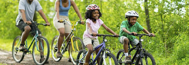 A family biking on a dirt trail in the woods.