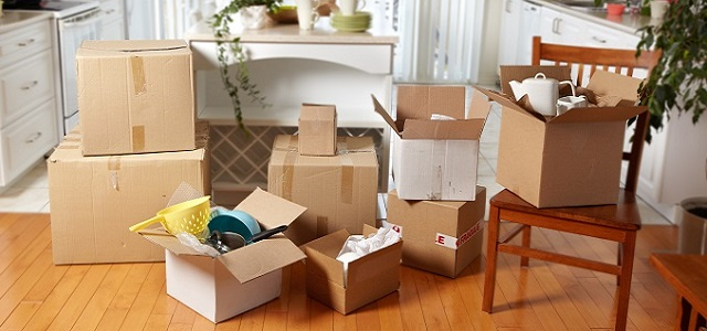 A collection of packed moving boxes and furniture in a kitchen.