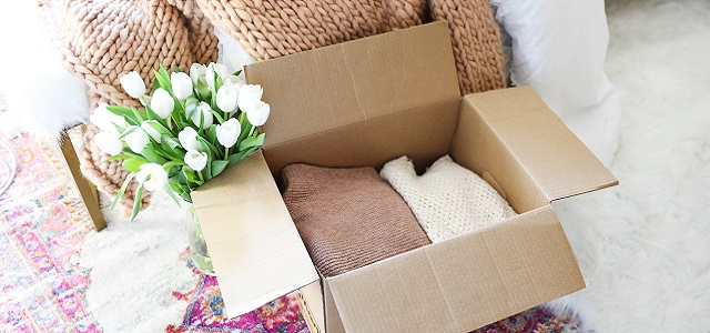A cardboard moving box filled with pastel colored sweaters.