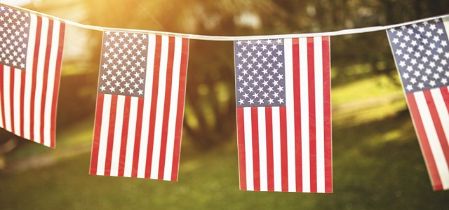 Plastic American flags on a white string.