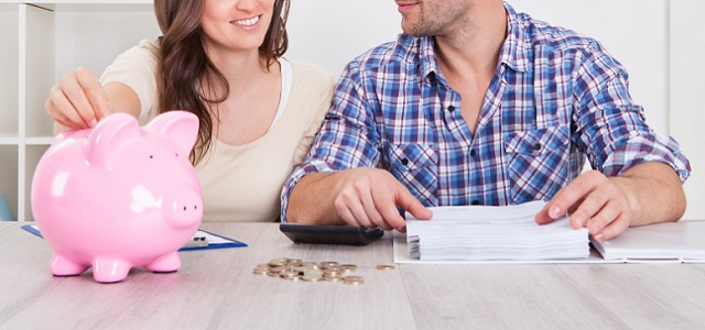 A man and woman sitting with a piggy bank planning finances.