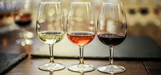 Three wine glasses on a wooden table during a wine tasting.
