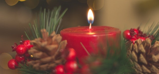 lit candle with christmas decor