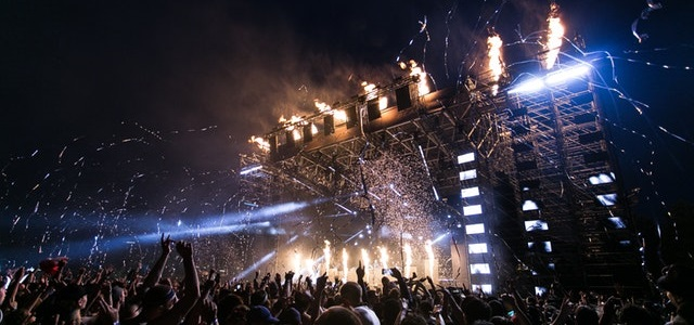 a stage with lights and streamers, behind an excited crowd with their arms in the air.