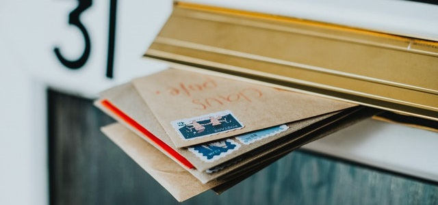 brown paper envelopes with stamps hanging outside of a mailbox.