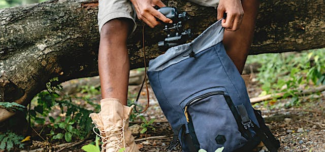 a hiker retrieving his camera from his blue backpack.