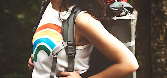 woman wearing a rainbow shirt and a hiking backpack.