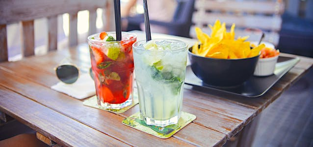 a set of tropical drinks on a table aside chips and dip.