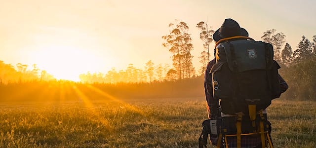 man hiking through a field at sunset with a backpack on.