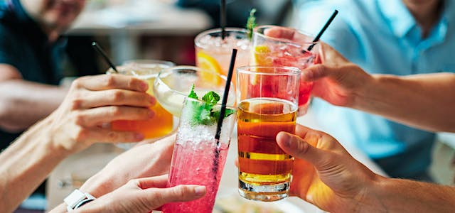 A group of friends clinking their tropical drinks with one another.