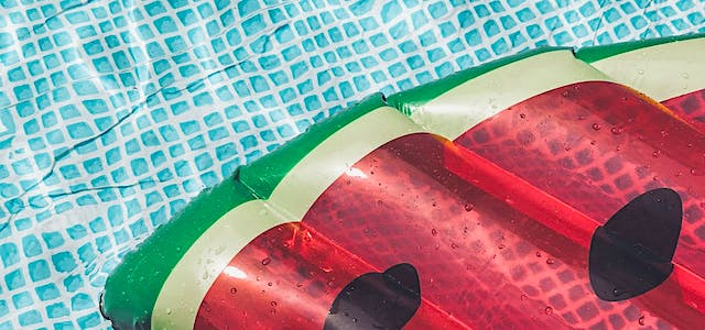 watermelon pool float in a blue pool on a summer day.