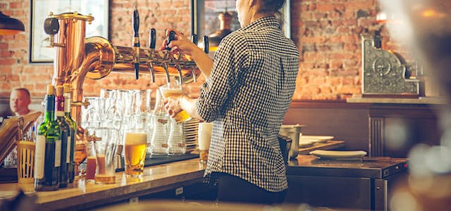 woman standing behind the bar pouring a beer for a customer.