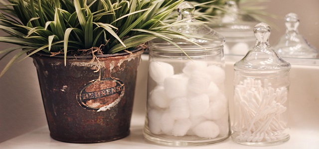 cotton swabs in a glass jar next to a leafy green plant.