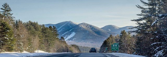 viewpoint from a car on a highway leading to franconia notch state park and a scenic mountain view.