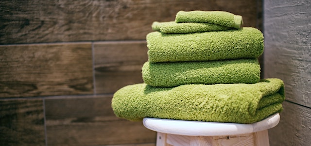 green folded towels sitting on a stool in a tiled bathroom.