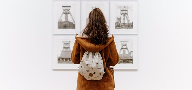 a woman observing a set of images in an art gallery.