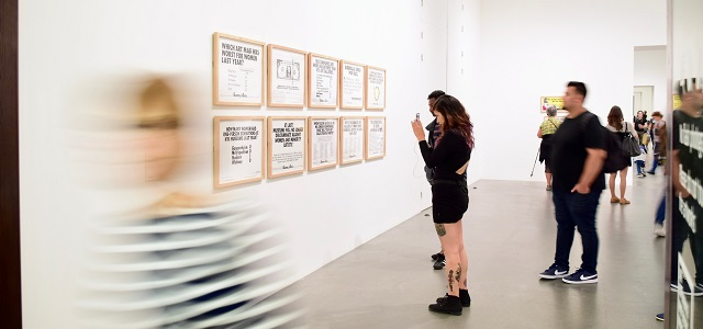 a person taking photos of an art display on the wall in a gallery